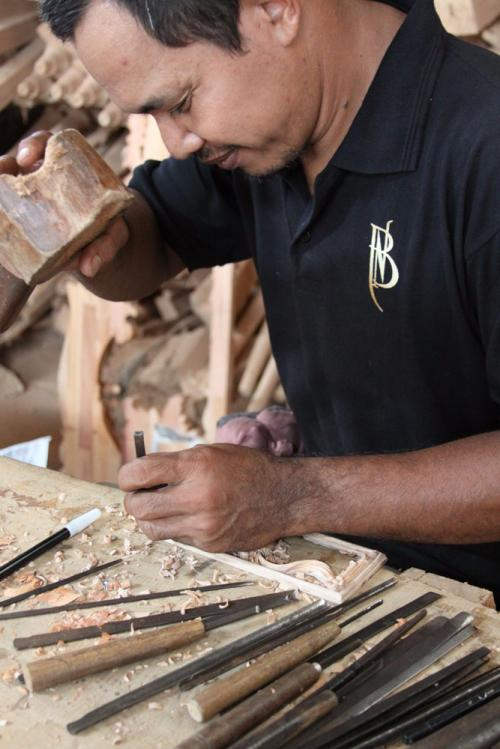 Hand carving one of the central frieze panels featuring a traditional urn with swag and tails