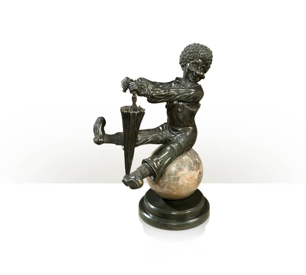A verdigris brass figure of a clown