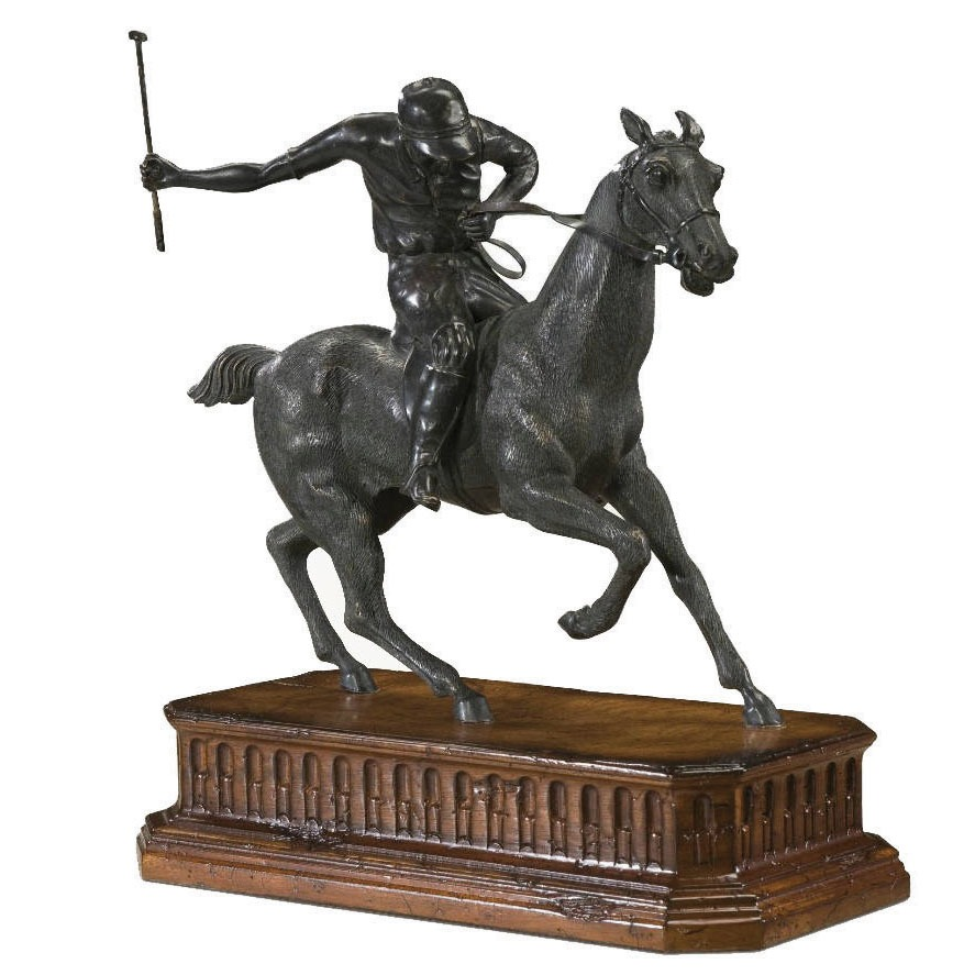A brass statue of a race horse and jockey
